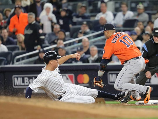 Aaron Judge slides into first during the fourth inning