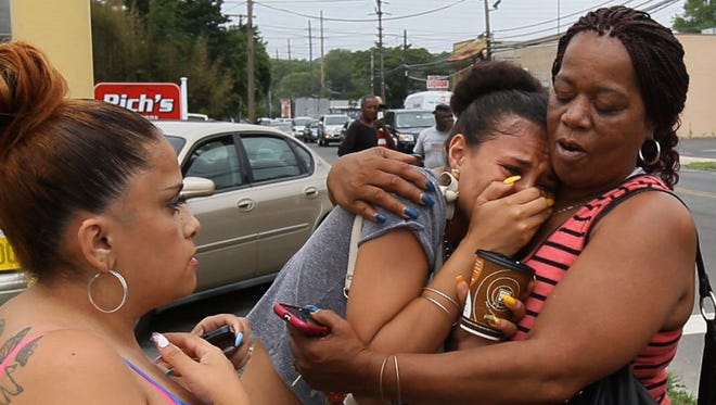 An unidentified woman is comforted at the scene of a shooting June 16, 2015, in Asbury Park, N.J., in which an off-duty police officer killed his ex-wife as their youngest child watched.