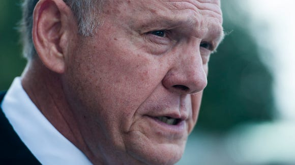 Roy Moore talks with media after leaving the Alabama