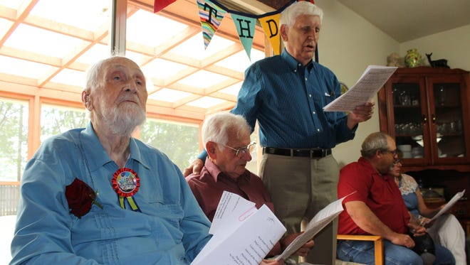 Lloyd Boyll listens as friends and relatives sing at his 100th birthday party Sunday at his home. Leading the singing was Jack Boyd, standing.