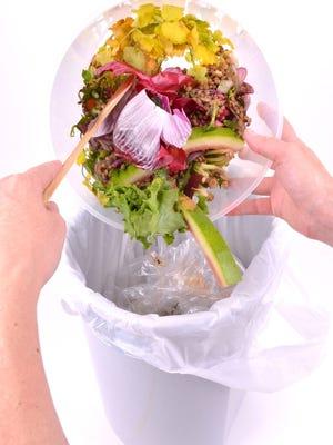 Emptying Leftover Food Scraps into a Rubbish Bin