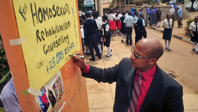 """Ugandan anti-gay activist Pastor Martin Ssempa posts up a public notice offering """"rehabilitation"""" for homosexuals at Uganda's National Theatre in Kampala on Tuesday, Feb. 25, 2014."""