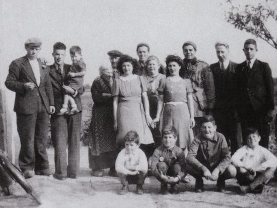 James Megellas, third from right in back row, poses