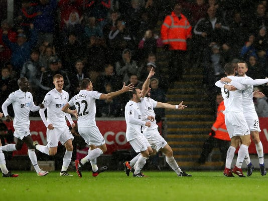 Swansea City's Fernando Llorente, second right, celebrates scoring his side's second goal of the game with team-mate Swansea City's Gylfi Sigurdsson, right, during the English Premier League soccer match between Swansea City and Sunderland at the Liberty stadium in Swansea Wales. Saturday, Dec, 10, 2016. (Nick Potts/PA via AP