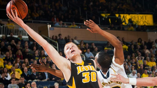 Iowa forward Aaron White (30) attempts to hook in a layup past Michigan guard Muhammad-Ali Abdur-Rahkman (12) in the first half on Thursday.