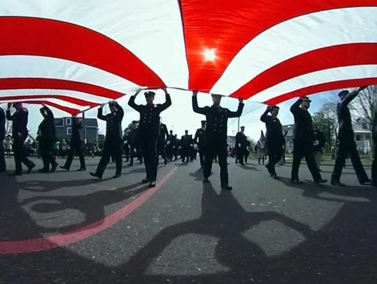 Firefighters from the Jersey Shore carry a large American