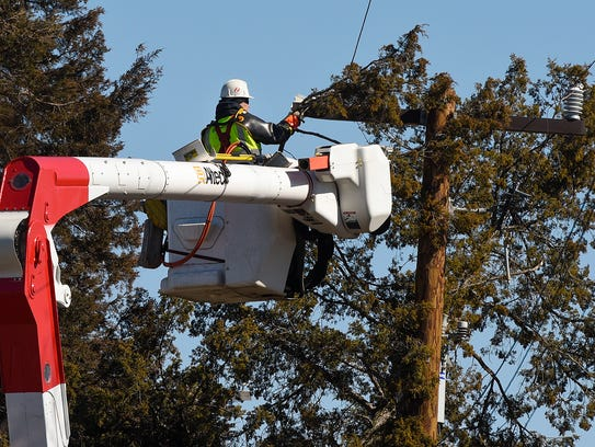 Crews from Xcel Energy remove a large tree that fell