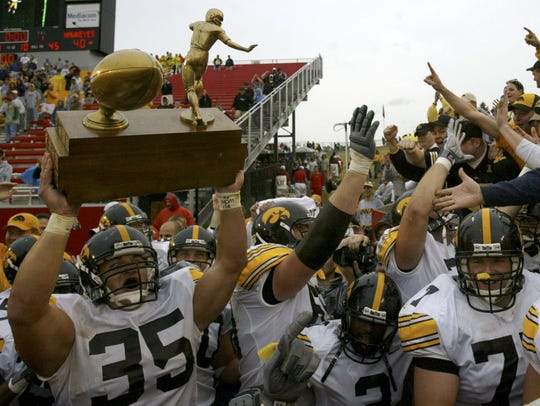 """With the black-and-gold faithful chanting """"Hawkeye State! Hawkeye State!"""" Iowa's Erik Jensen hoists the Cy-Hawk Trophy after the Hawkeyes beat Iowa State, 40-21, Sept. 13, 2003, in Ames."""