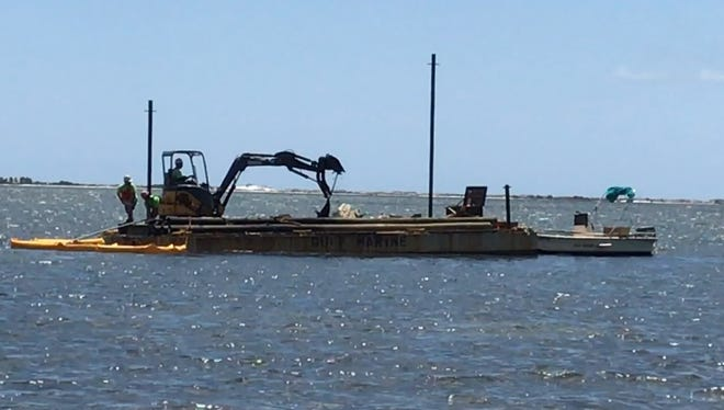 A contractor lifts a derelict boat out of the Santa Rosa Sound on Wednesday, April 26, 2017.