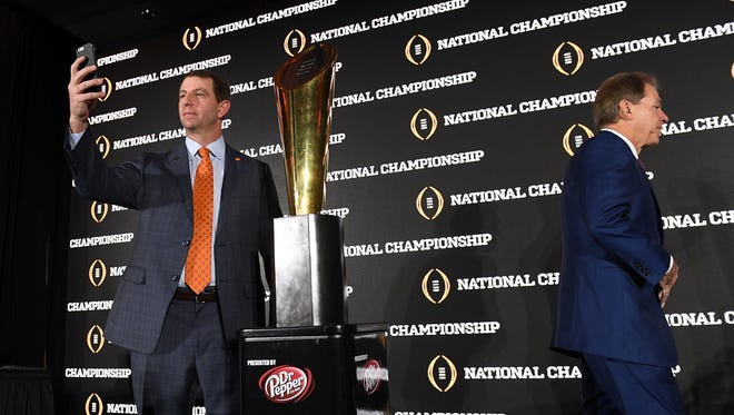 Clemson head coach Dabo Swinney, left, poses for a selfie with the National Championship trophy as Alabama head coach Nick Saban walks away after the head coaches press conference in Tampa on Sunday, January 8, 2017.