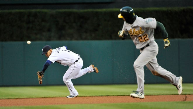 Athletics' Josh Reddick (22) heads to third base and then scores after this single by Jed Lowrie is deflected by Tigers shortstop Jose Iglesias in the fourth inning.