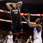 Miami Heat's Michael Beasley, center, goes up for a dunk past 76ers' Jerami Grant, right, during the first half Wednesday.