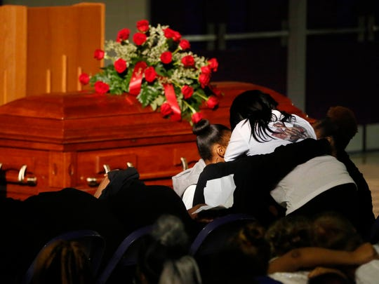 Katrina Johnson, mother of slain 16-year-old Kedarie Johnson, embraces her family as they play a song for Kedarie on Wednesday, March 9, 2016, during a funeral service at Burlington High School in Burlington, Iowa.