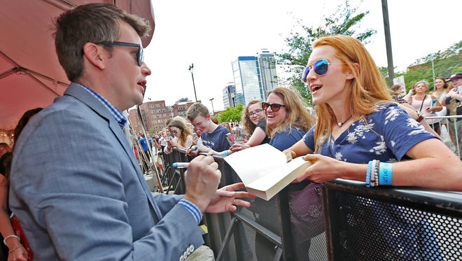 "John Green, left, signs a copy of ""Paper Towns"" during a 2015 promotional event at Old National Centre."