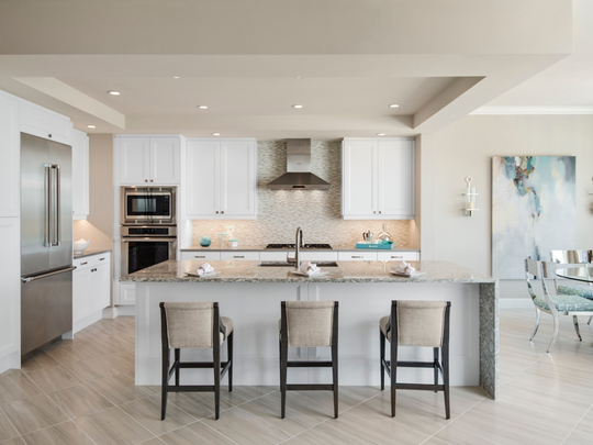 This state-of-the-art kitchen is appointed with classic white Irpinia cabinets and a quartz-topped, one-sided waterfall edge island, then balanced by stainless appliances and fixtures from Grohe, Thermador and Kohler.