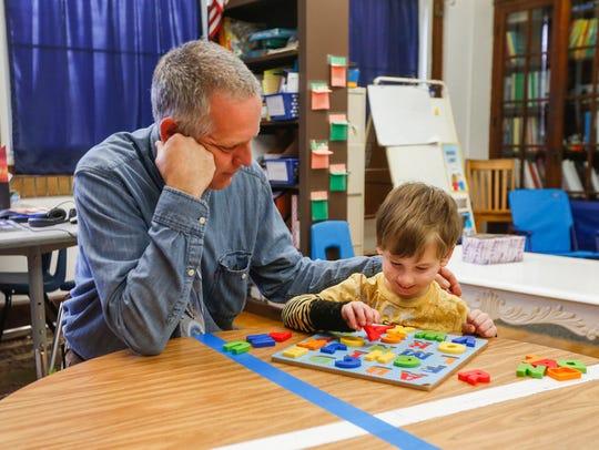 Principal David Martin works with kindergartener Grey