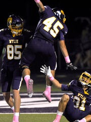 Wylie High School tight end Lane Ross (left) watches as fullback Nathan Moore jumps in the air to congratulate teammate Hayden Keidl Friday Oct. 13, 2017, not yet realizing that Keidl had been injured scoring his touchdown against Brownwood High School. Wylie won in overtime, 45-38.