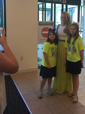 Miss Louisiana April Nelson (center) is greeted by two Fleur Di Lis Princesses on Monday as she returns from competing in Miss America.