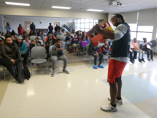 Quentin Gause, a former Bishop Kearney football star  is now a linebacker with the Denver Broncos, reads a book about Muhammad Ali to a group at David Gantt Recreation Center.