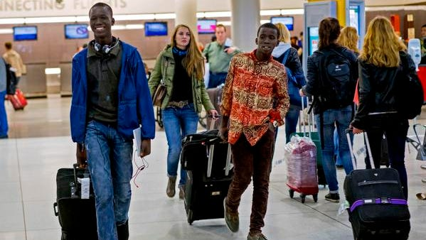 Johnson Nellon, left, and his brother Thomas Nellon of Liberia smile at their mother Saturday in the arrivals area at John F. Kennedy International Airport in New York, upon seeing her after passing through customs. The brothers received a health screening upon arrival from a flight they connected with in Europe, the first day of Ebola screening at JFK.