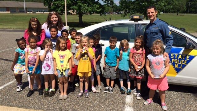 Children from Brenda DeCesero's kindergarten class at Milanesi Elementary School visit with State Trooper Mark Compagna.