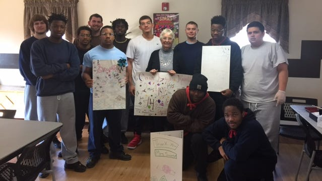Beth Swartz poses for a pictures with teens at Lighthouse Youth Center who made oversized cards to thank her for her volunteer work at the center during a recent farewell party. Swartz volunteered at Lighthouse for 22 years and was instrumental in putting together the library and art program.