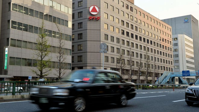 Vehicles pass before the Tokyo office of Japanese drugs maker Takeda Pharmaceutical in Tokyo on April 8, 2014.