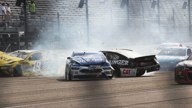 Sprint Cup Series driver Ryan Blaney (21) and Sprint Cup Series driver Patrick Carpentier (32) tangle in turn one following a restart of the race during the running of the 23rd annual Brickyard 400, Sunday, July 24, 2016.