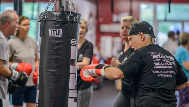 Participants learn to punch at Rock Steady Boxing, a program for people with Parkinson's disease, at Sweat Therapy Fitness.