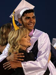 Elias Vigil gives Mrs. Simmons a hug after receiving his Deming High School diploma.