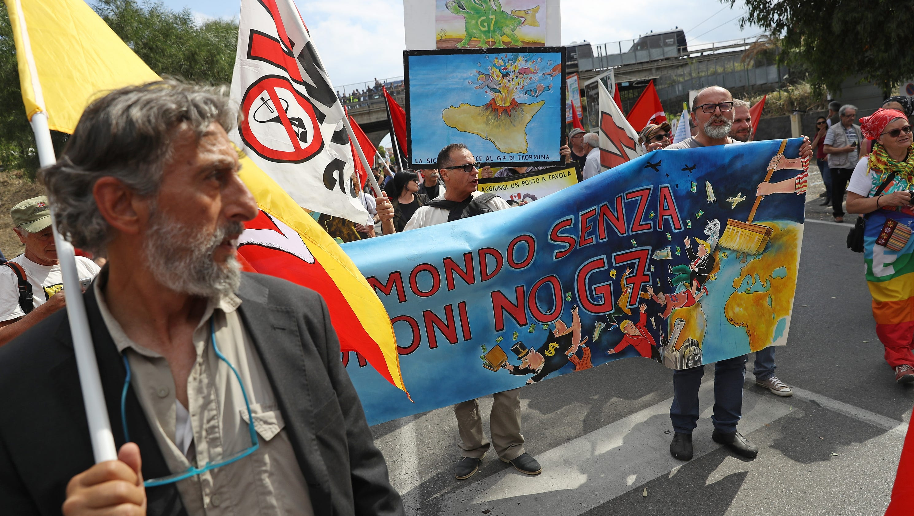 G-7 summit protesters rail against immigration, capitalism as leaders fly overhead