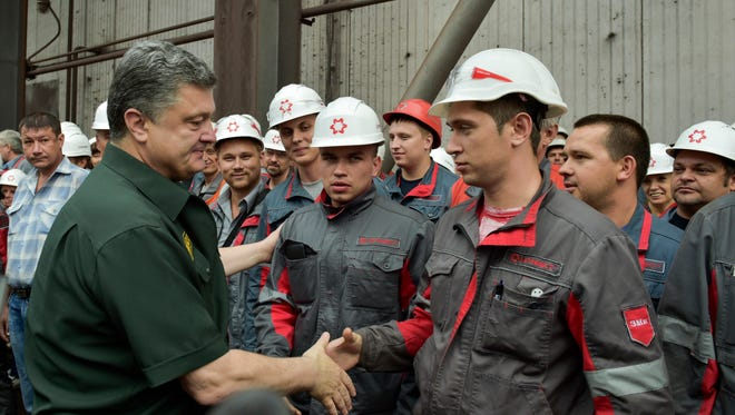 Ukrainian President Petro Poroshenko greets workers during a surprise visit to a steelworks in the southern coastal town of Mariupol, Ukraine, on Sept. 8.