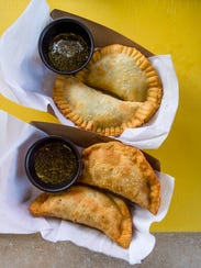 A spinach and cheese, top, and beef empanada with chimichurri