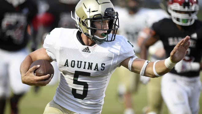 Aquinas' quarterback James Schlegel tries to keep his distance from the Harlem defense as he runs with the ball during football action at Harlem High School in Harlem, Ga., Friday evening September 4, 2020.