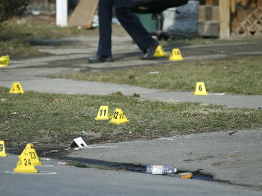 Evidence markers placed at a shooting scene on Fourth Street in Rochester Wednesday.