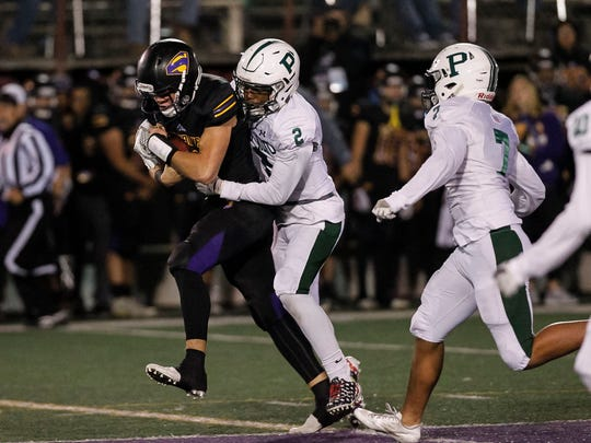 Salinas' Brett Reade controls the ball on a quarterback keeper as Palo Alto's Junacio Henley tackles during a Central Coast Section: Open Division I playoff football game between the Salinas Cowboys and the Palo Alto Vikings at the Pit at Salinas High School on Friday, November 17, 2017 in Salinas, Calif. Vernon McKnight/for The Californian