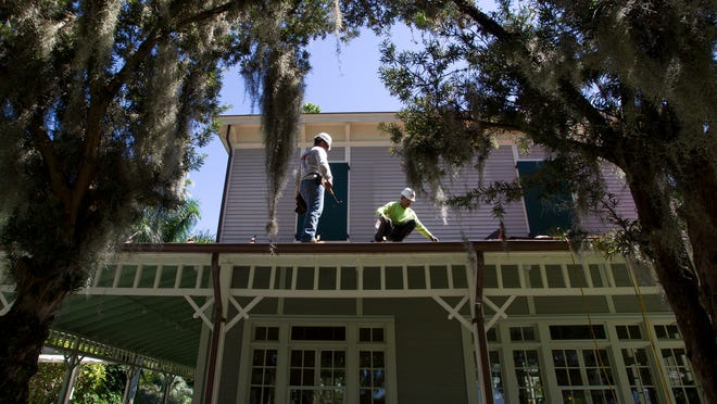 Juan Lara and Edwardo Marichal prepare the roof of the Seminole Lodge Guest House for new shingles as Thomas Edison's guest house undergoes maintenance Thursday in Fort Myers.
