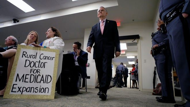 Senate Majority Leader Thomas K. Norment, Jr., R-James City, right, walks past a sign held by Dr. Monica Morris, MD, the Medical Director of the Solari Radiation Therapy Center at VCU Community Hospital in South Hill, Va., as he enters a meeting of the Senate Finance Committee in Richmond, Va., Tuesday, May 29, 2018.