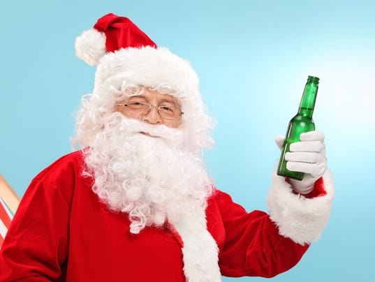 Santa Claus holding beer seated on a sun lounger