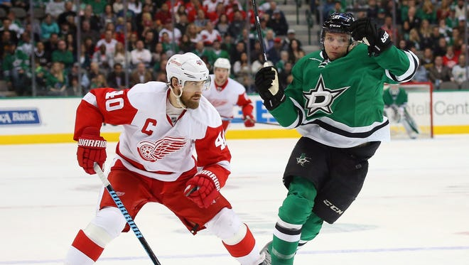 Detroit Red Wings' Henrik Zetterberg skates the puck against Dallas Stars' Antoine Roussel in the first period at American Airlines Center on Saturday.