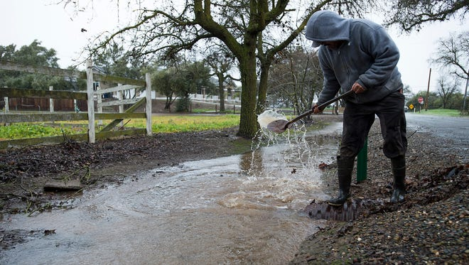 Jose Flores clears storm drains during a storm on Sunday, Jan. 8, 2017, in Wilton, Calif.