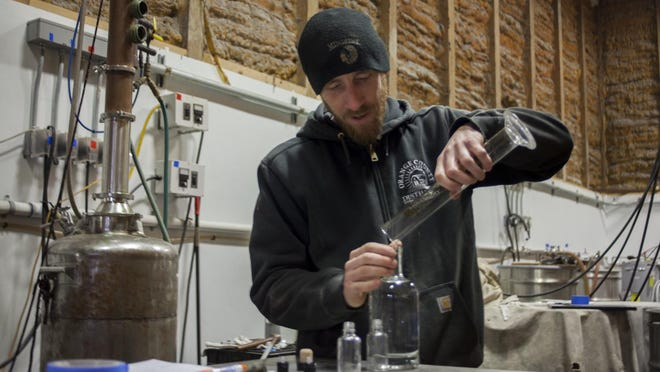 John Glebocki, co-owner of Orange County Distillery, pours ethanol into a bottle at the production facility in Goshen on Thursday. Orange County Distillery will be using its 192-proof ethanol – distilled on-site from grains grown in the Black Dirt – to make 50 gallons of hand sanitizer.