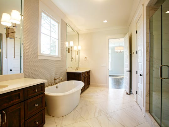 With marble floors, a walk-in marble-lined shower, a free-standing soaker tub and his-and-hers vanities, this master bath has a spa feel.
