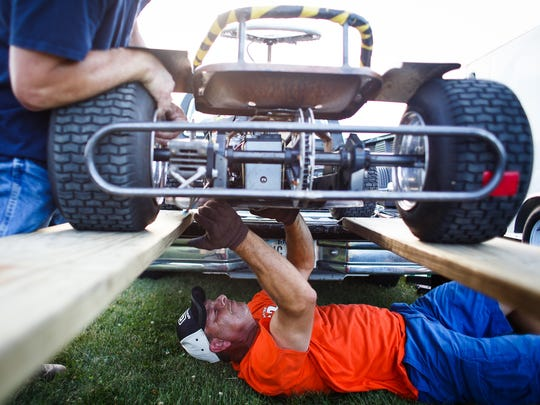 Marty Kunkel, 51, of Newton, bottom and his brother Dewey, 53, of Des Moines, work on Marty's lawn mower before racing at River Bottom Raceway on Saturday, July 16, 2016 in Carlisle. A stock car racer before his kids were born, Marty began racing lawn mowers as a way to keep racing but admits that working on the mowers is his favorite part.