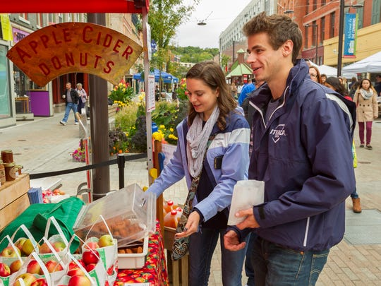 Ithaca College seniors Stephanie Waite, of Binghamton, and Johnston Tucker, of New Canaan, Connecticut, buy apple cider doughnuts Friday from the Littletree Orchards stand at the Apple Harvest Festival.