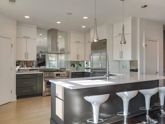 Professional appliances in this gourmet kitchen include a six-burner gas stove with griddle and dual ovens. Floor-to-ceiling cabinets and adjoining pantry provide ample storage.