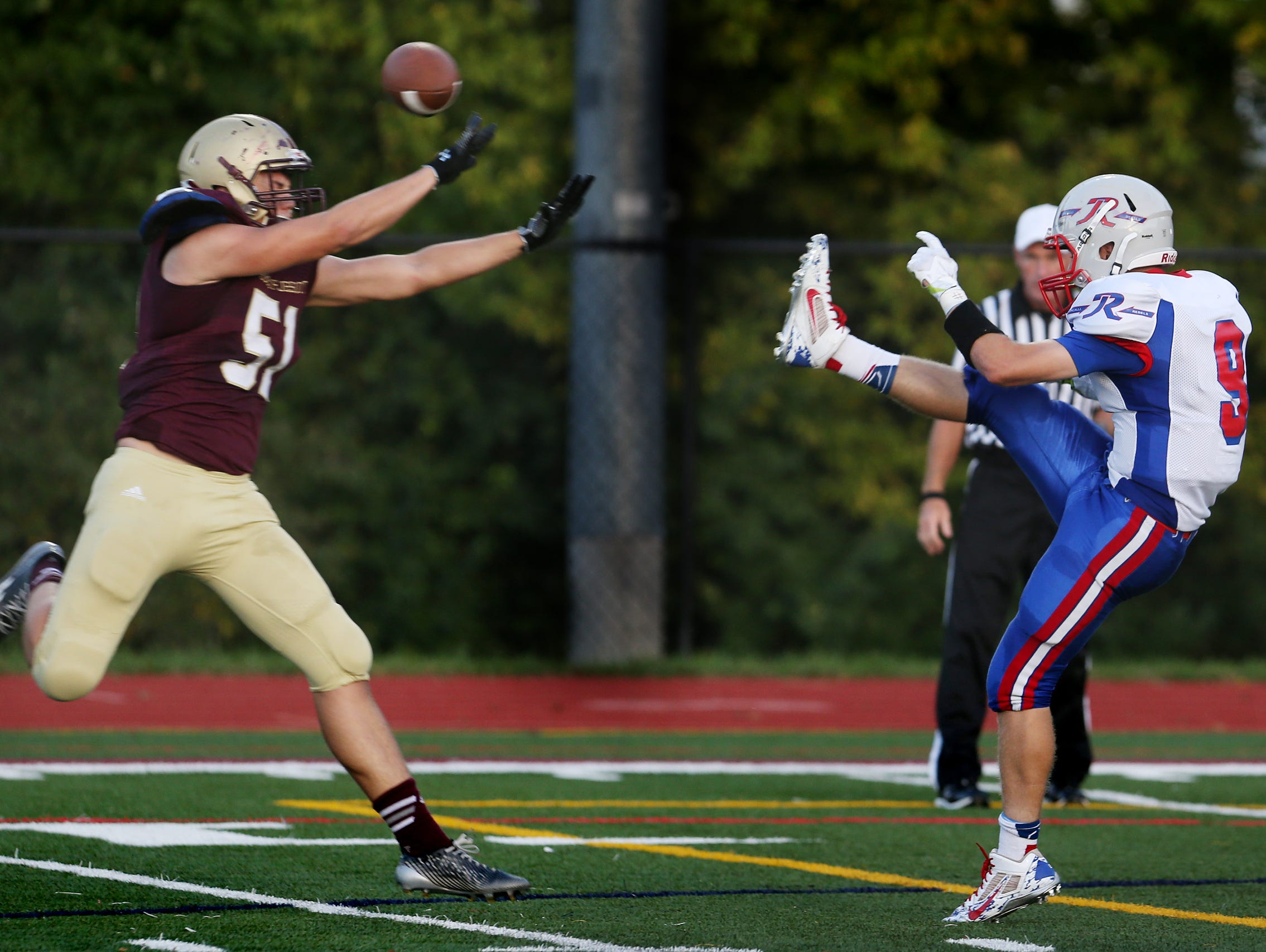 Brebeuf Braves' DL Gerard Carthy blocks a punt by Roncalli's Robbie Strader deep in Rebel territory, after which teammate Ethan Beatty fell on the ball in the end zone for the game's first score at Brebeuf, on Friday, September 26, 2014.