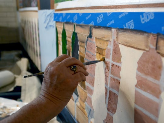 Artist Jenny Walker paints a mural Monday, June 13, at Great Lakes Italian restaurant in Fort Gratiot Township.