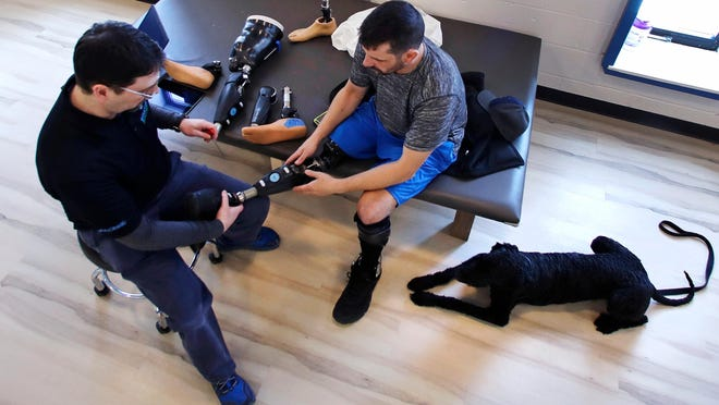 Prosthetist John Warren attaches a foot toFucarile's microprocessor controlled prosthetic knee during a visit to the Medical Center Orthotics and Prosthetics in Boston.