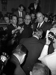 Jack Ruby's attorney Melvin Belli (center) speaks to